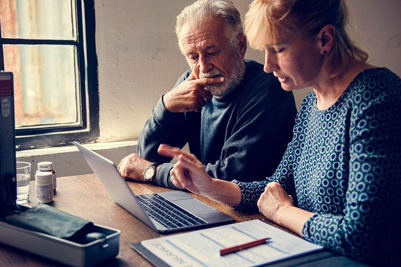 elderly couple researching grants information online